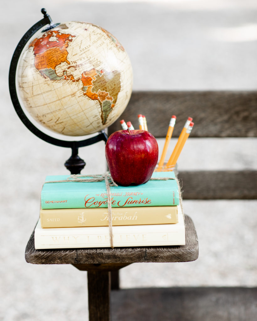 A globe, a stack of books tied with twine, a red apple, and some yellow pencils sitting on top of an old wooden school desk.