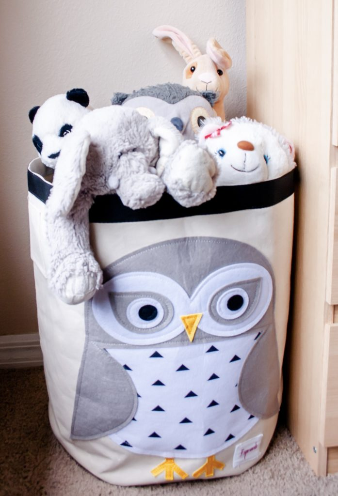 A cloth bag with an owl on front full of stuffed animals showing one way you can organize your children's toys.
