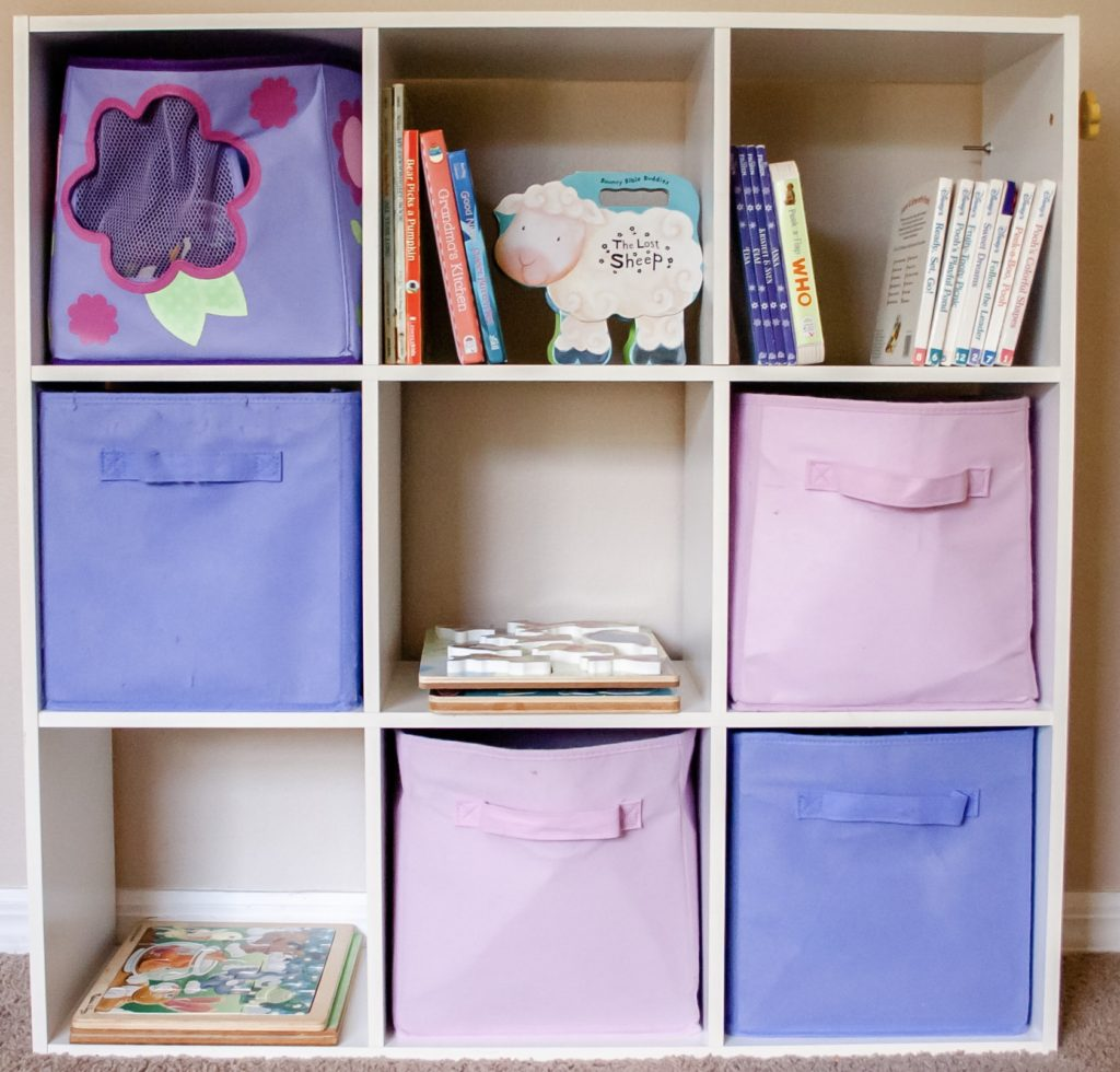 A 9 cube piece of furniture holding square, colorful bins, books, and puzzles showing one way you can organize children's toys.