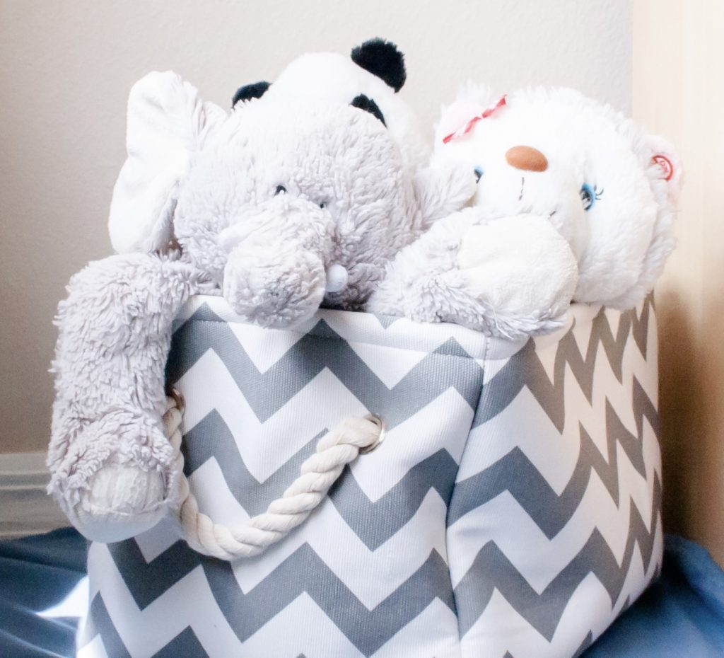 A zig zag basket filled with stuffed animals showing one way to contain children's toys.