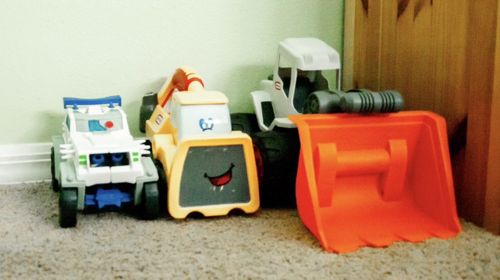 Children's trucks and tractors lined up against the wall, showing one way to contain these toys.