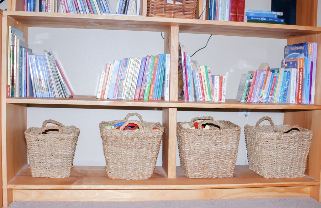 Woven baskets across the bottom shelf of a bookcase showing one way how to organize children's toys.