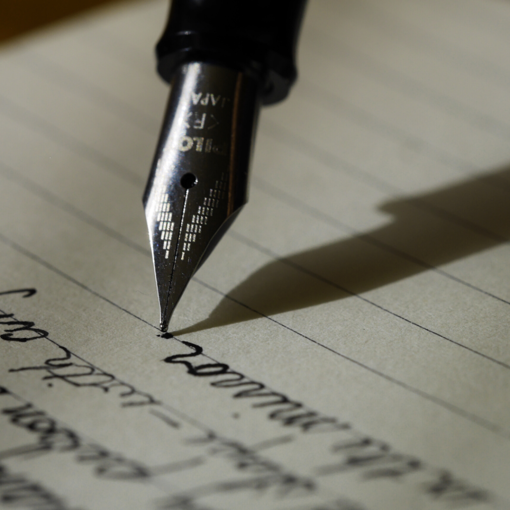 A fountain pen writing on paper in cursive.