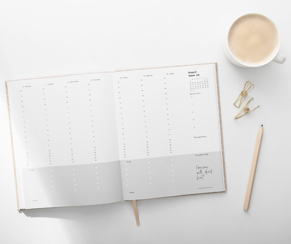 A calendar laying open on the table with a full cup of coffee and a pen sitting next to it.