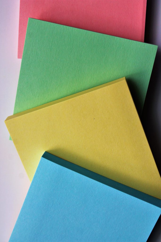Four pads of brightly colored post-it notes spread out waiting for you to start setting your goals.