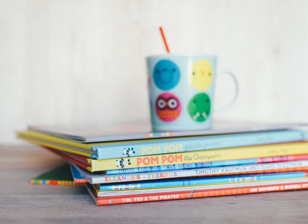 A cup sitting on top of a stack of easy reader books.