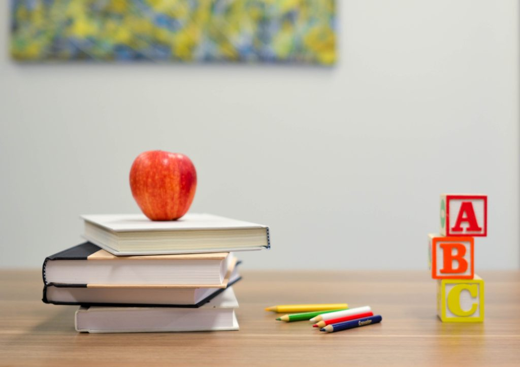 A red apple sitting on top of a stack of books to read.