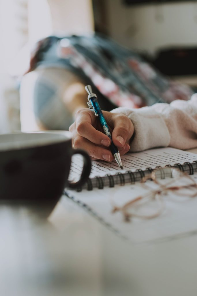 A person sitting and writing in their journal with a cup of coffee sitting next to them.
