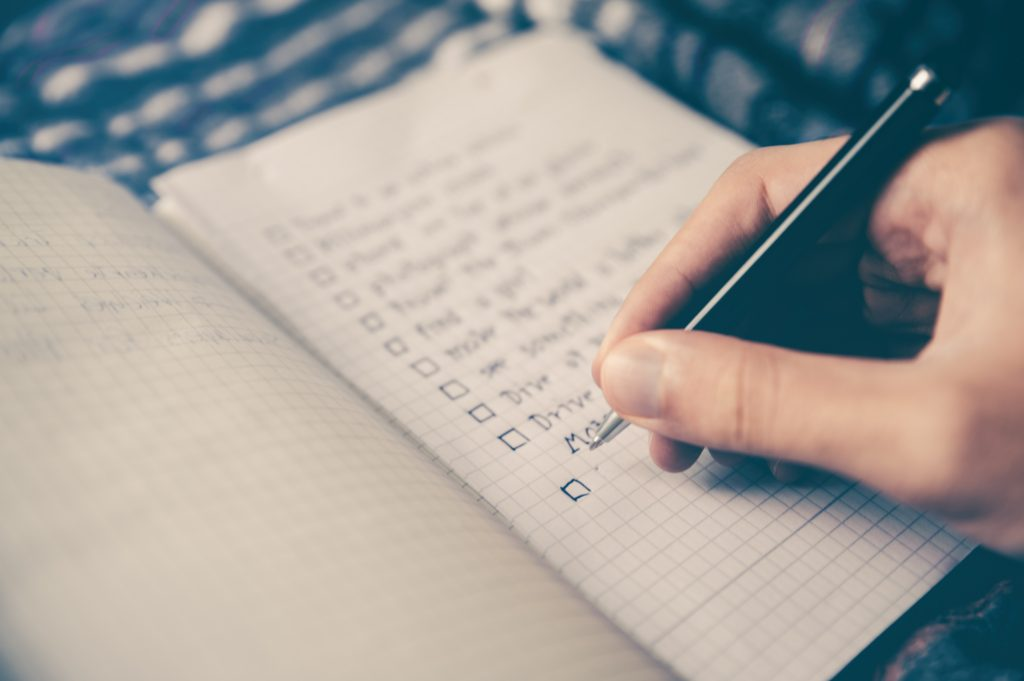 A person holding a pen above their journal with a list of items to do written inside.