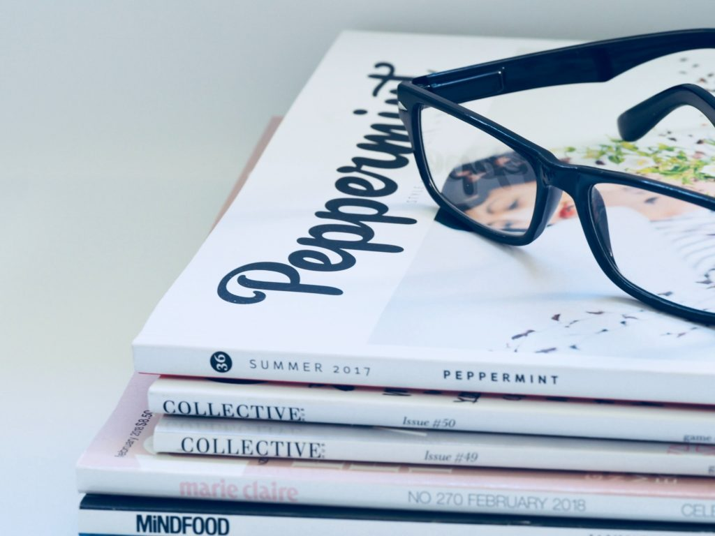 A pair of reading glasses sitting on top of a stack of children's books.