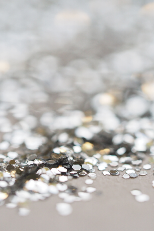 Silver glitter scattered over a table showing that it's very easy to get distracted when you're trying to get organized.