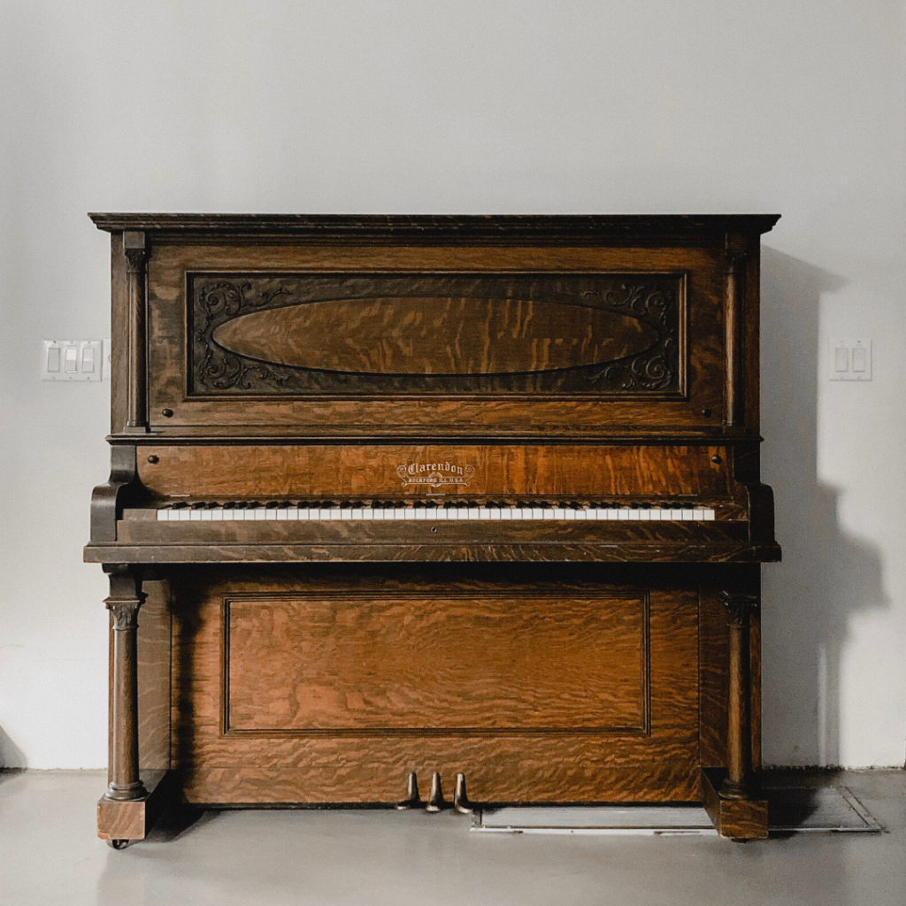 An upright wooden piano standing next to a white wall.