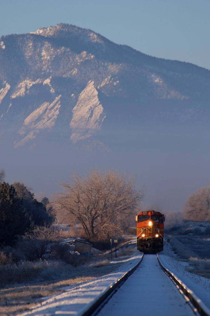 A view from the train tracks of a train coming straight at the camera with the mountains in the background.
