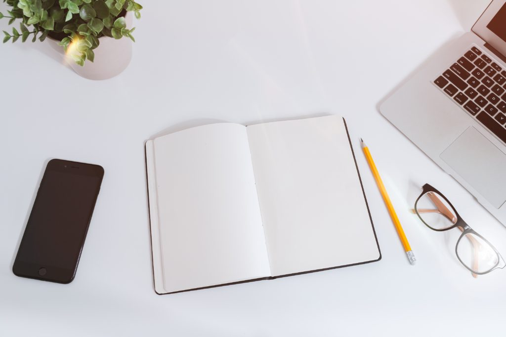 A notebook and pencil sitting on a desk alongside a laptop, smart phone, and a pair of glasses.
