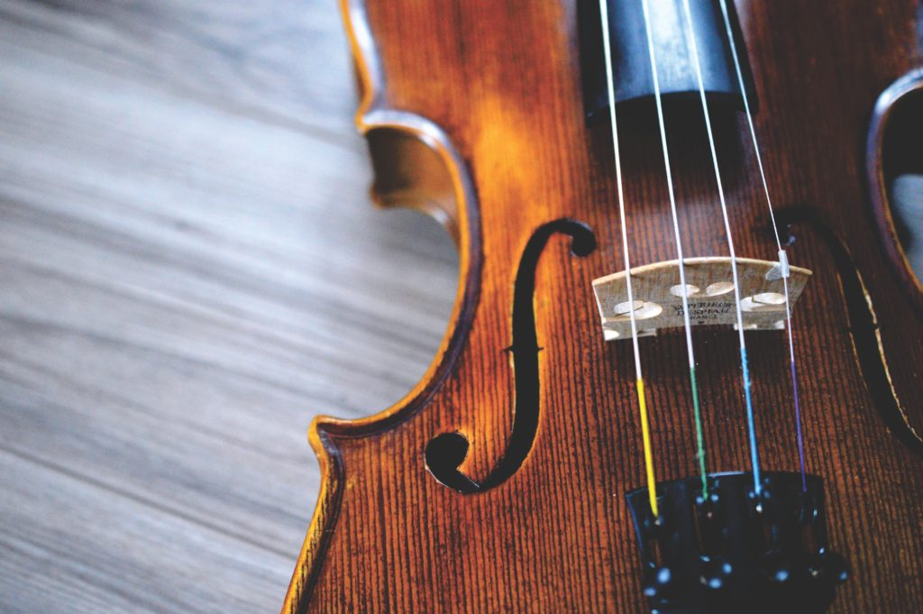 A close up picture of the body of a violin against a gray background reminding you that music can help you slow down and gain space.