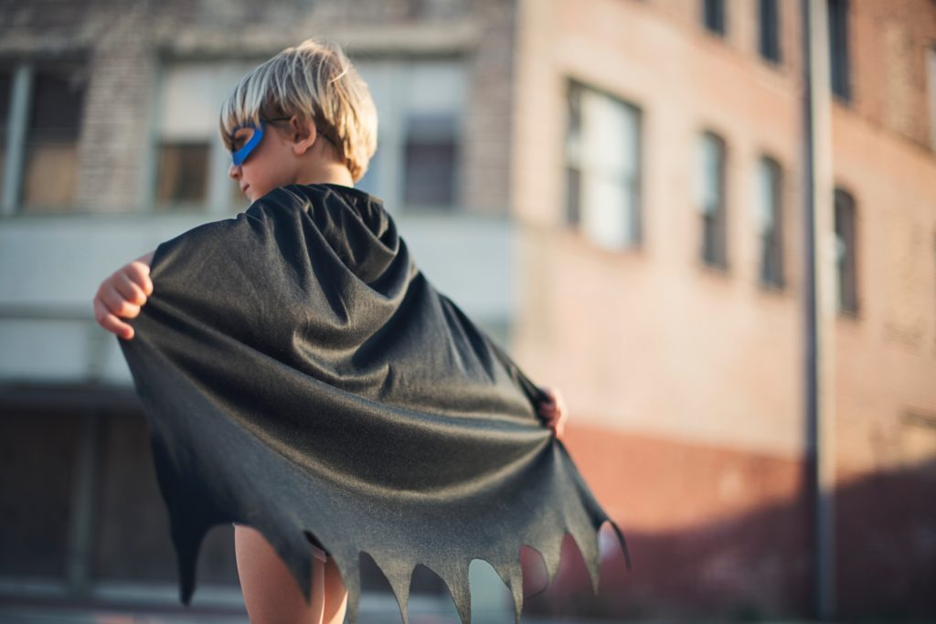 A young boy in a mask and super hero cape ready to take on the world.