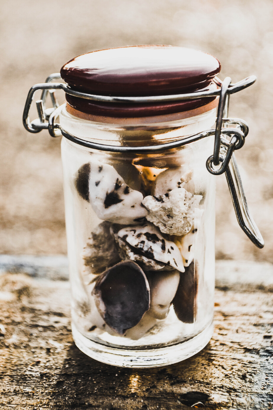 A glass jar filled with rocks representing a schedule.