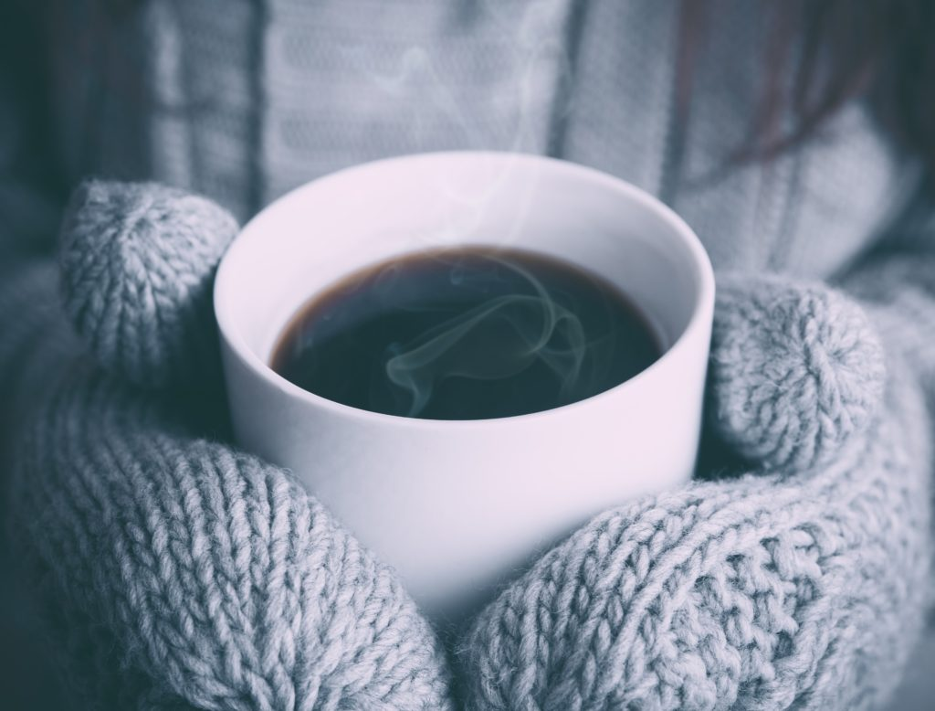 A pair of mittened hands curled around a hot cup of coffee.