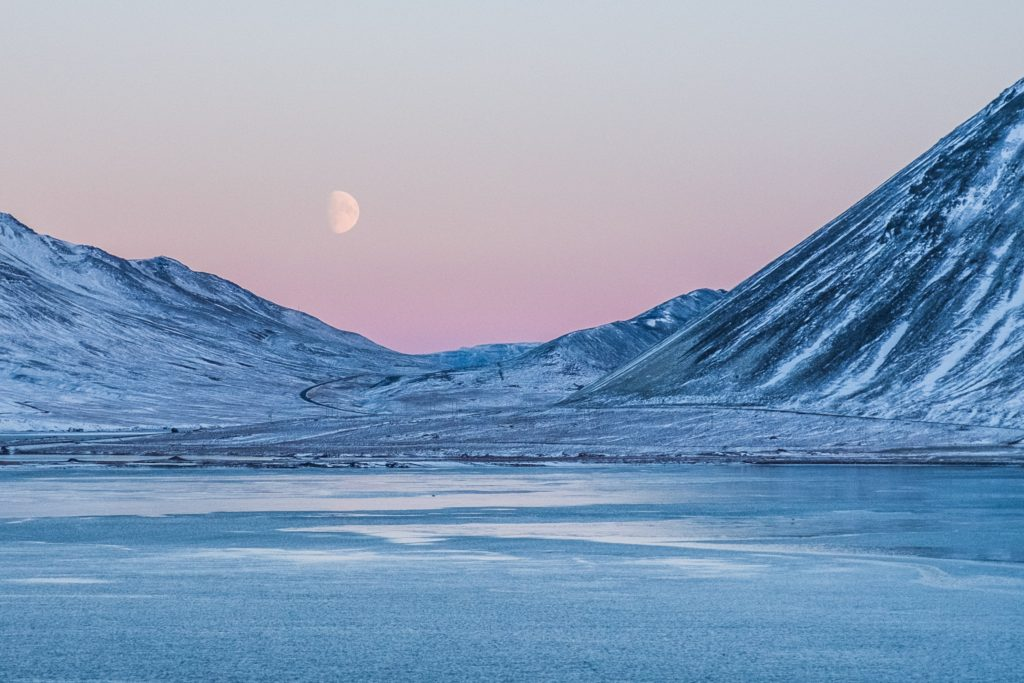 A beautiful winter scene of the moon rising over a frozen lake between two mountains.