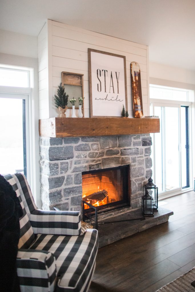 A cozy living room with a plaid chair pulled up close beside the fire as you look out over the winter landscape.