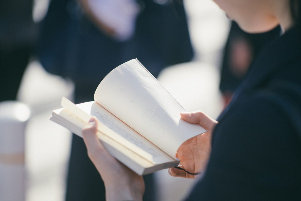 A girl holding a book and leafing through the pages.
