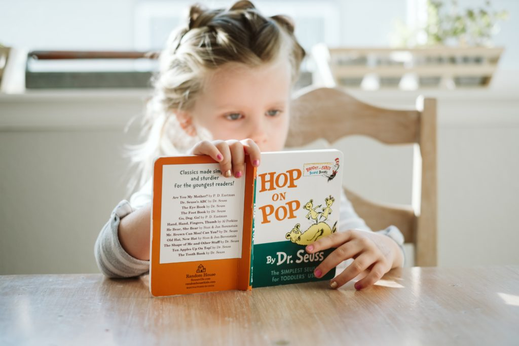 A young girl sitting at a table and reading Dr Seuss' book 'Hop on Pop'