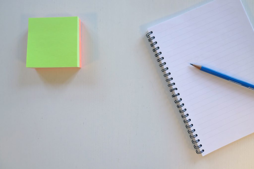 A notebook and a pen sitting next to a stack of sticky notes to help you create your schedule.