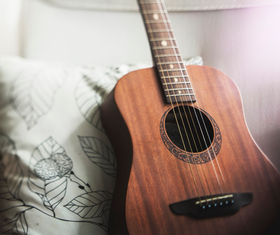 A polished guitar leaning against a black and white patterned pillow.