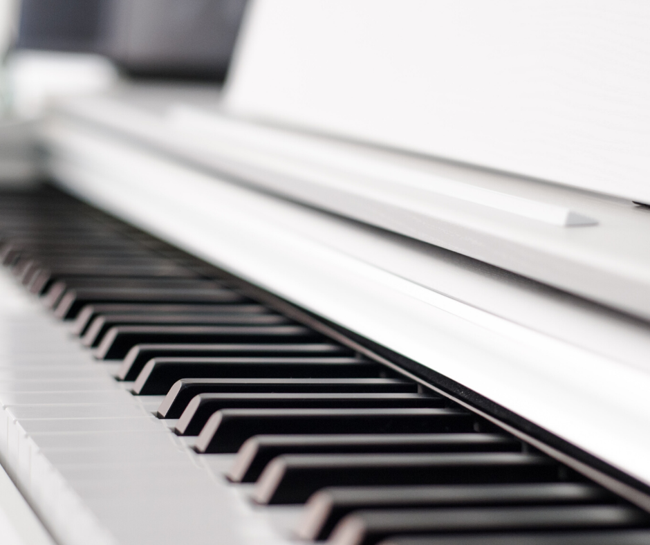 A close up of the keys of a piano.  The black and white keys stand out beautifully against the white frame of the piano.