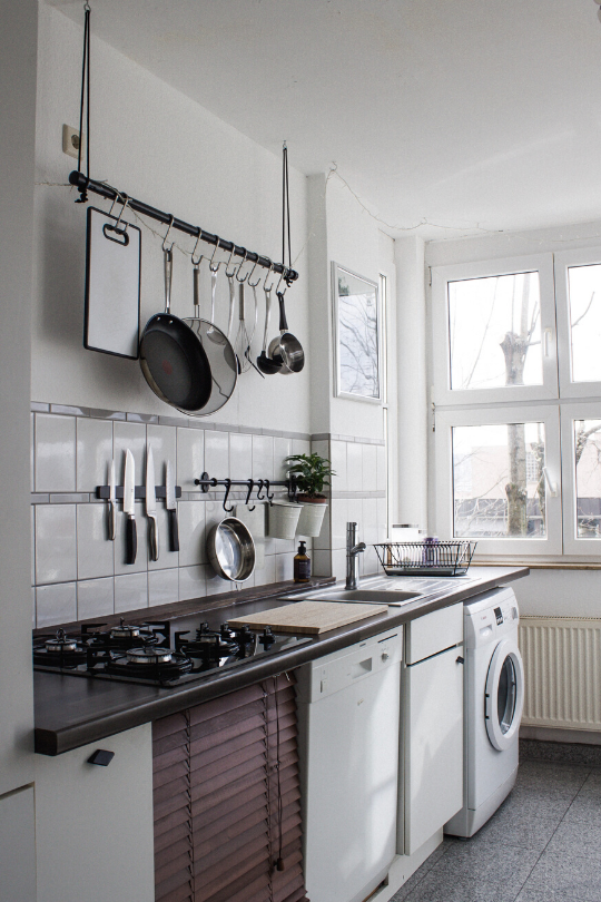 A small black and white kitchen with pots, pans, and knives hanging on the wall, showing that you can use your kitchen organization as decoration, too.