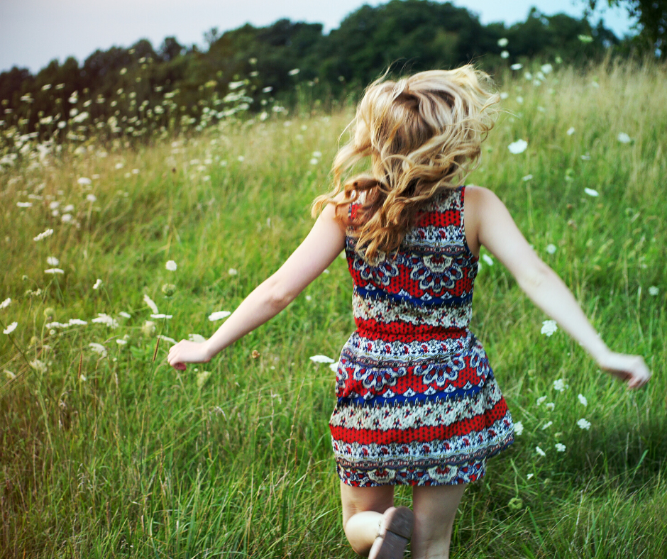 A young girl in a red striped dress running through a green field showing an activity idea for kids.