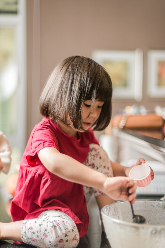 A young girl in a red shirt sitting on a kitchen counter and mixing something in a bowl, showing a non-screen activity for kids.