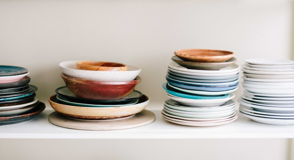 A colorful stack of bowls and plates on a shelf, showing that each kitchen will be organized a little differently.