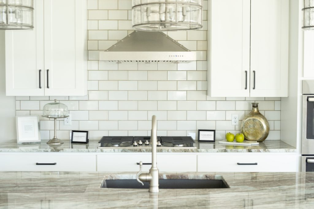 A white and silver professional looking kitchen giving yet another example of how to organize your kitchen.