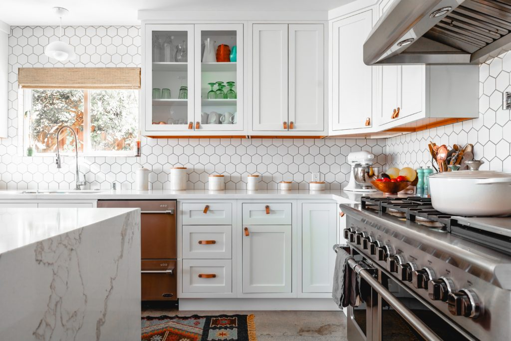 A square white kitchen with an island and subway tile backsplash, showing another way how to organize your kitchen.