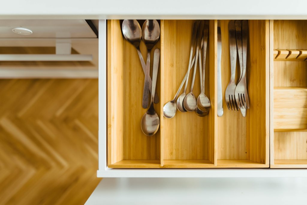 A picture of a bamboo silverware divider inside a white drawer with a wooden floor beneath, showing one possibility of how to organize your kitchen drawers.