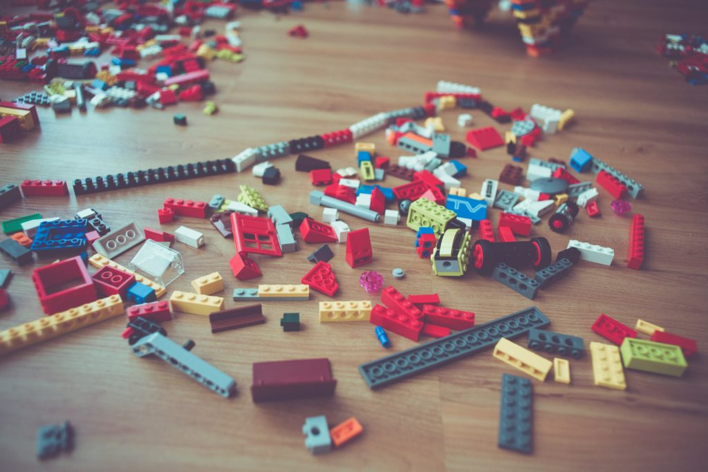 A bunch of LEGOs sitting on a wooden floor, in process of being played with.
