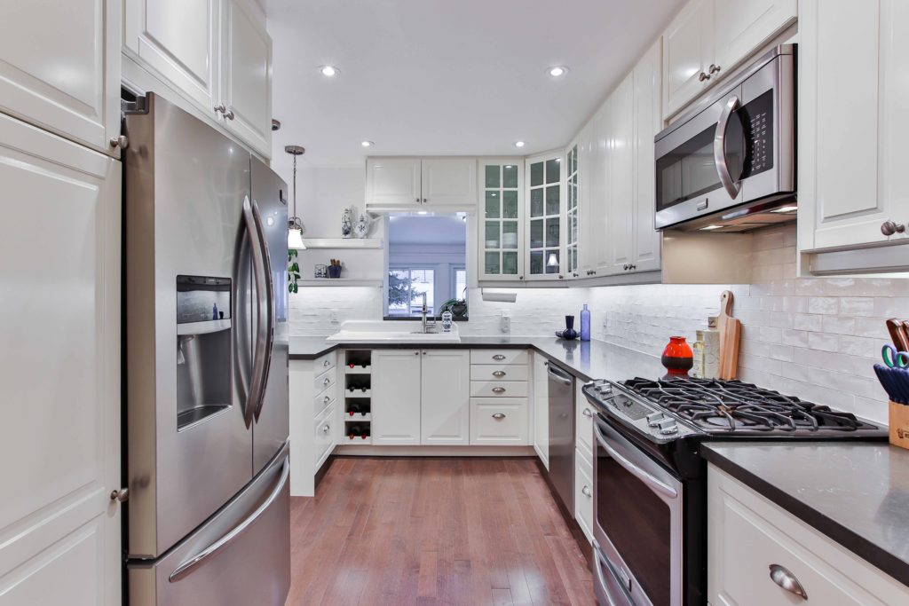 A beautiful picture of a long, rectangular silver and white kitchen.