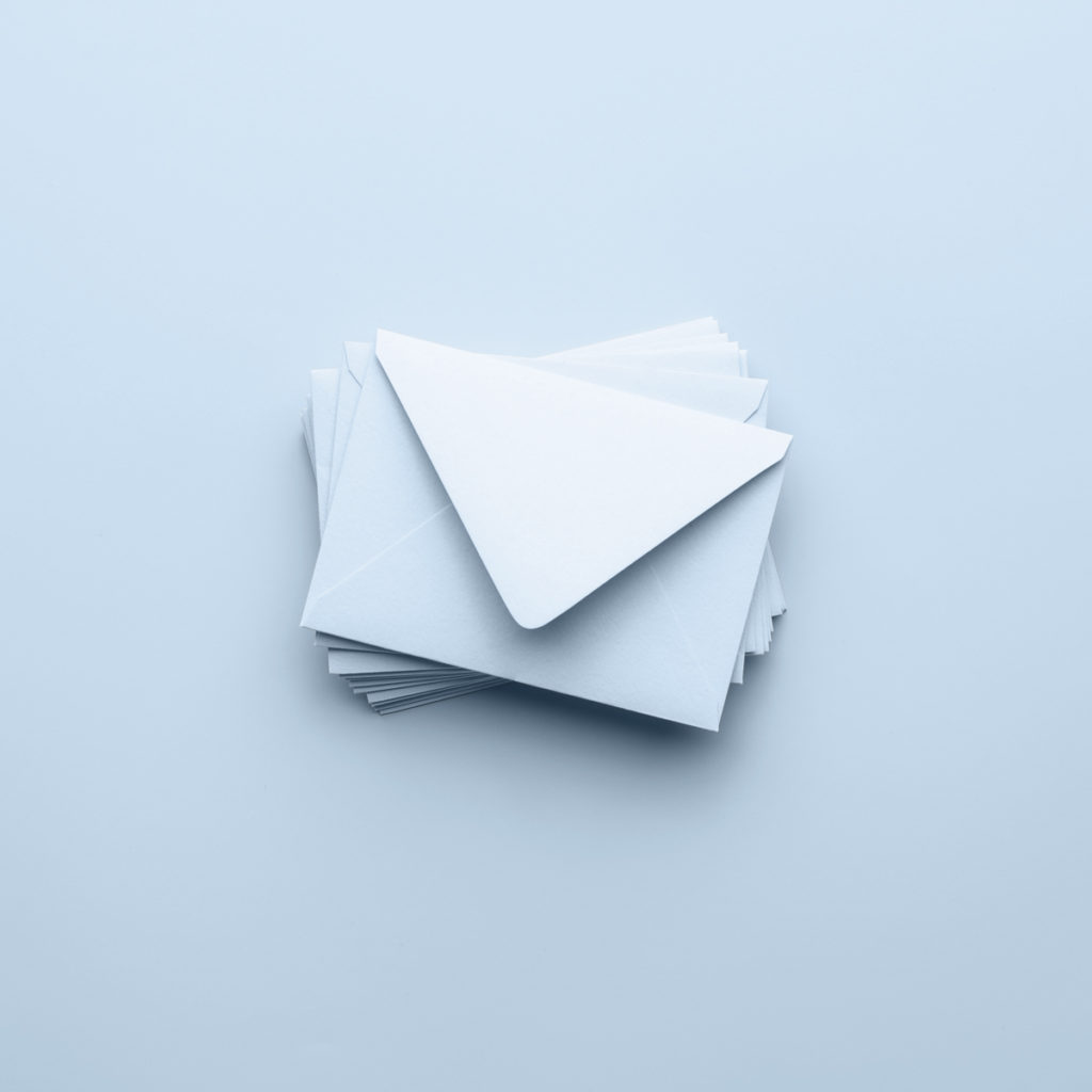 A stack of empty white envelopes sitting on a blue background, like the one used in The Empty Envelope.