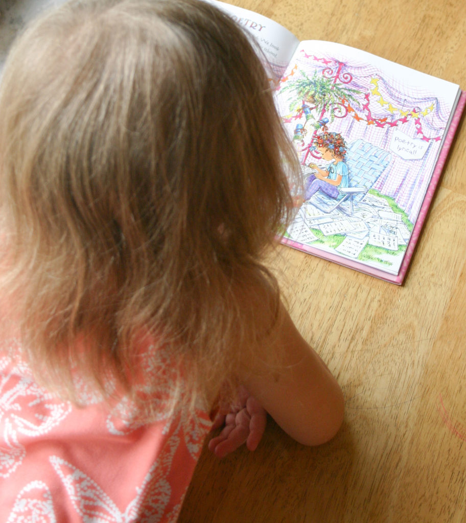 A young girl laying on her stomach and reading a Fancy Nancy children's book.