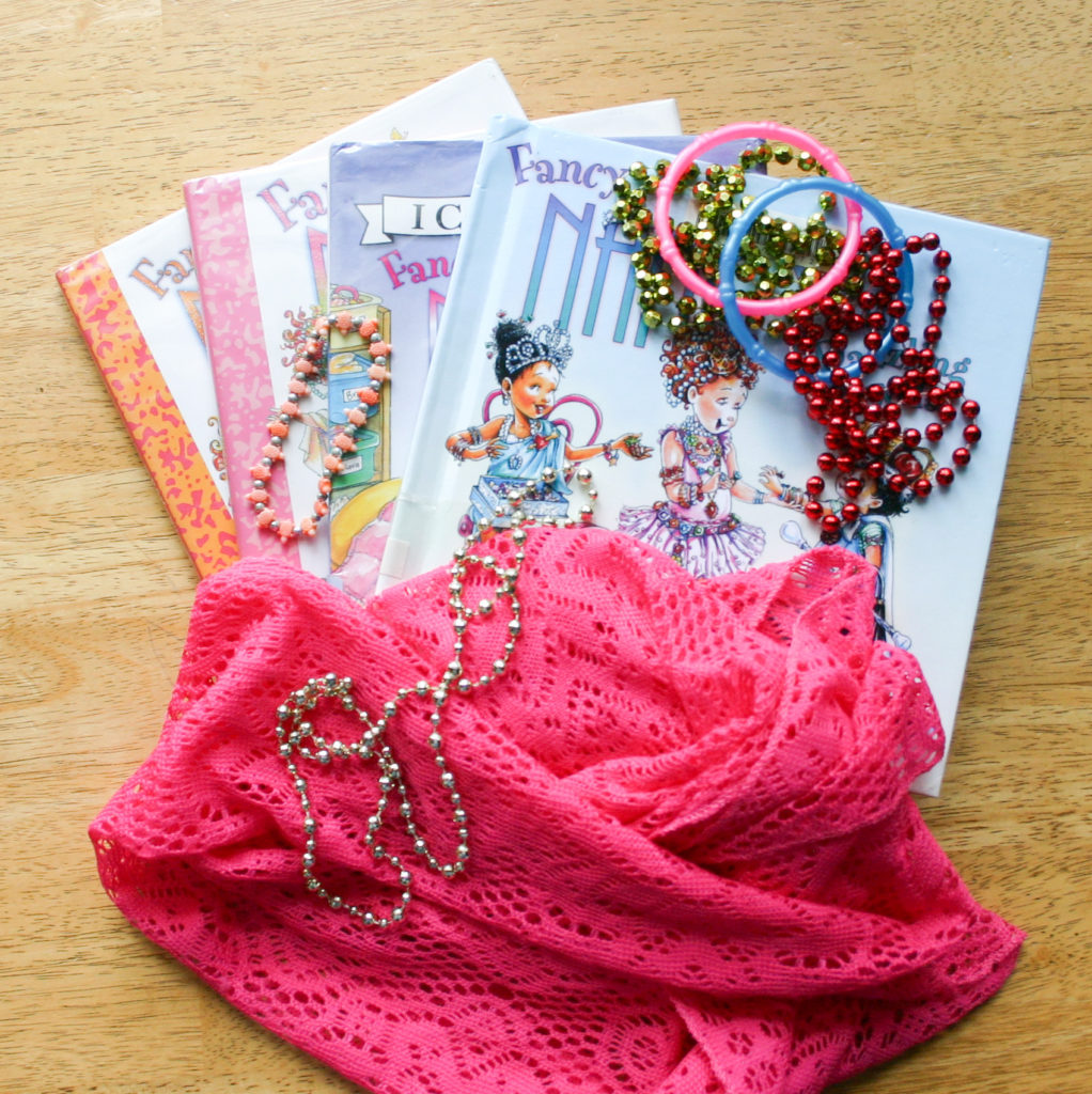 A few Fancy Nancy children's books fanned out with a scarf and dress up jewelry around it...just to be fancy!