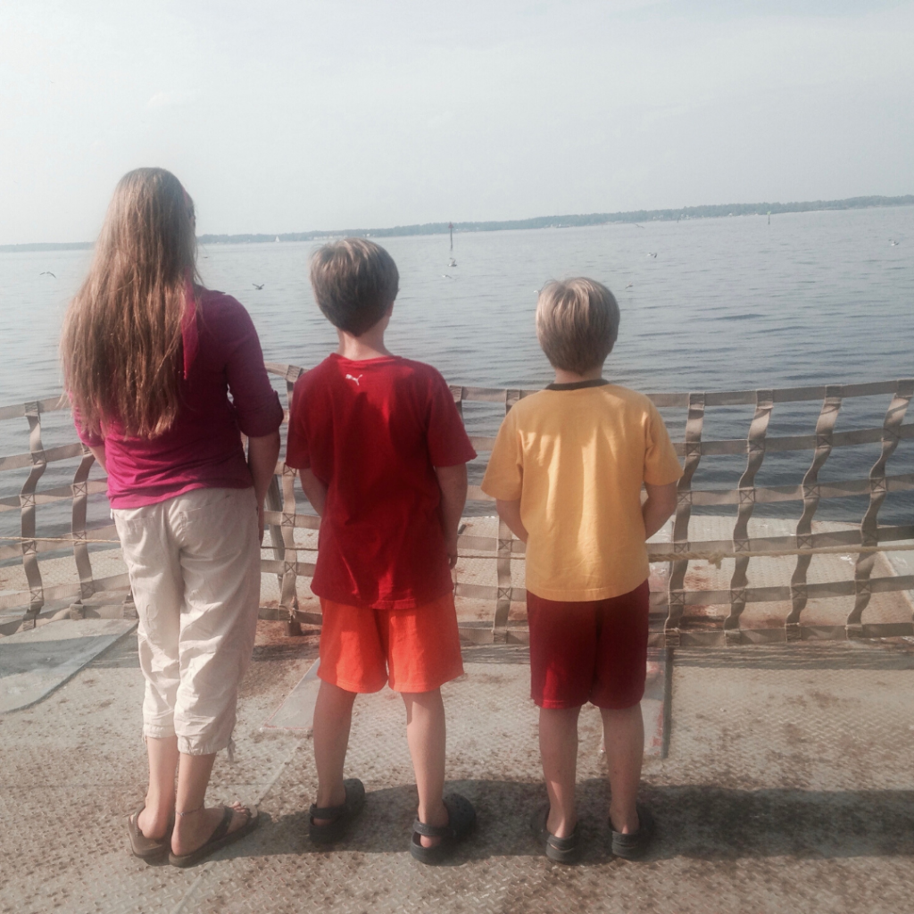 Three siblings standing and looking out at the water.  No conversation is needed when there is this much connection!