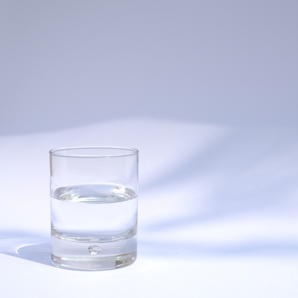 A glass of water sitting against a blue background reminding you that drinking water can help save money on your grocery bill.