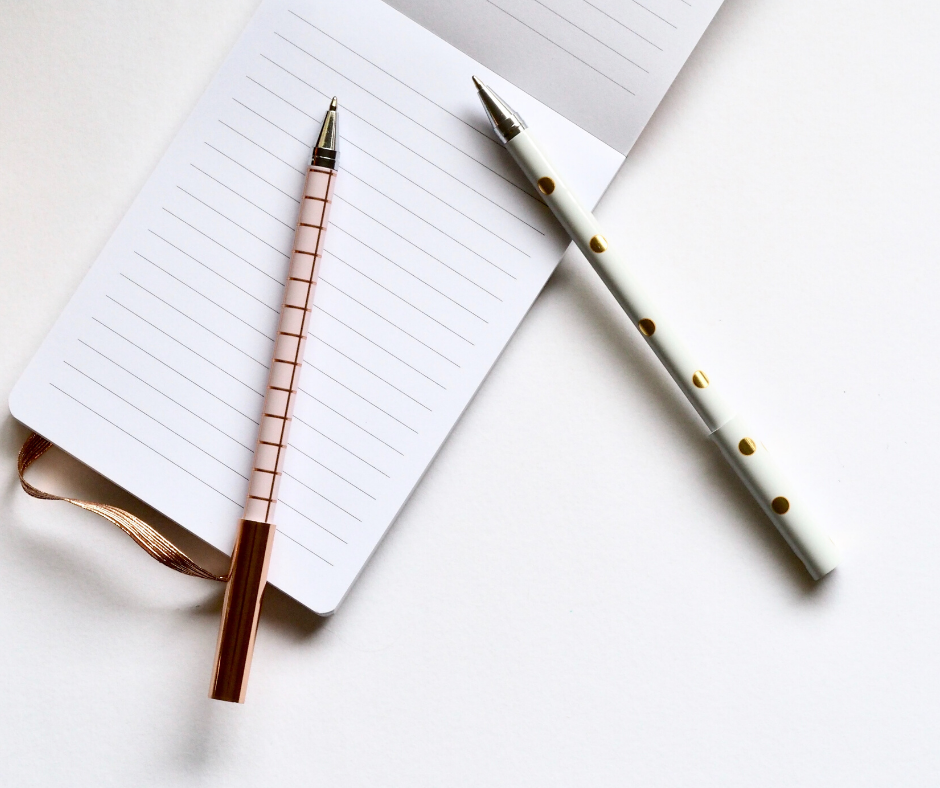 A notebook with a couple pens sitting on it, reminding you that a grocery list can help you save money on your grocery bill.