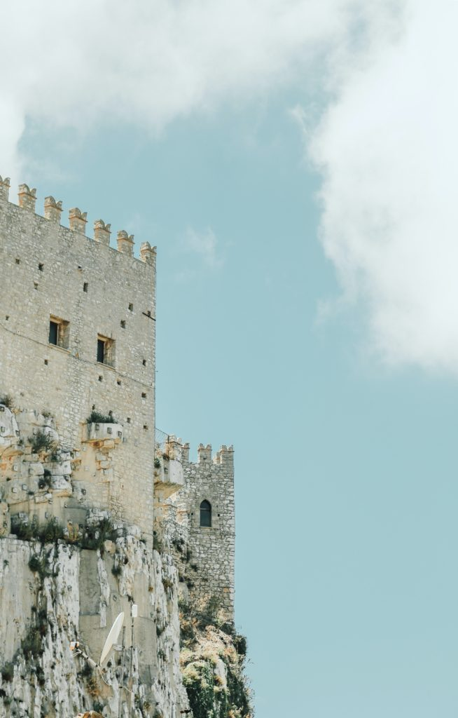 A castle tower set against a blue sky with white clouds, like the castle tower in The Deadly Dungeon.