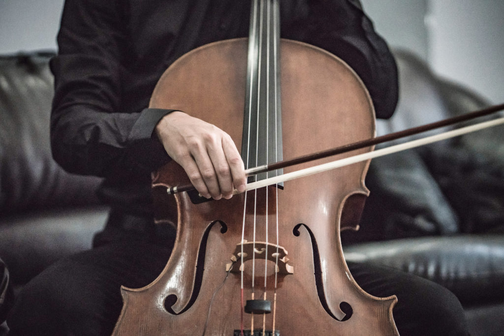 A person wearing a black shirt and playing a cello.
