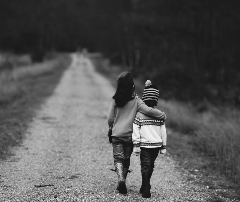 Two siblings walking down a road in  a black and white photo, enjoying their connection with each other.
