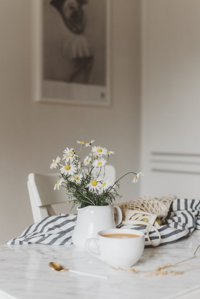 A kitchen table with a blue striped bag, a vase of flowers, and a cup of coffee on it.