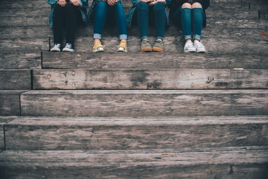 Four pairs of feet, clad in jeans can be seen as the people sit at the top of some stairs enjoying the relationship with each other.