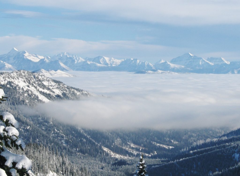 A view from high up in the mountains with thin clouds hanging like a veil, shadowing your view.